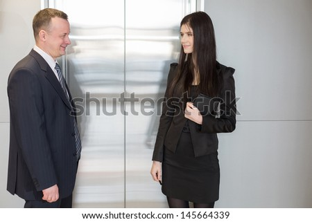 Man and woman in business suits waiting for elevator - stock photo