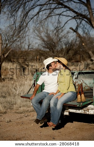 Man and woman in cowboy hats kissing on back of pickup truck - stock photo