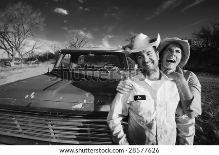 Man and woman in cowboy hats with old truck - stock photo