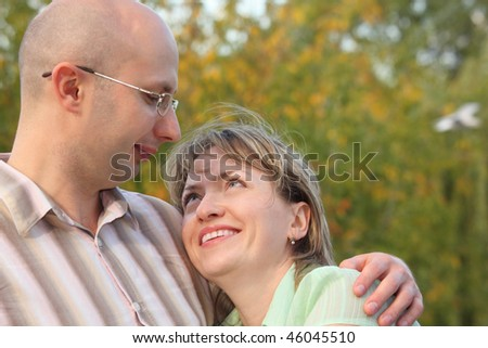 man and woman in early fall park. man is embracing smiling woman and looking at her - stock photo
