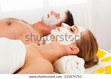 Man and woman in face masks lying back on clean white towels in a spa relaxing - stock photo