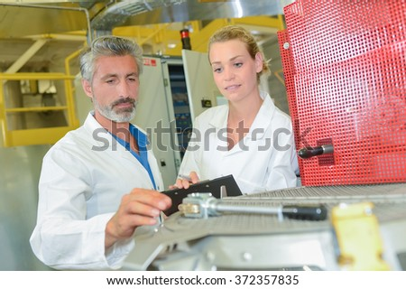 Man and woman in factory - stock photo