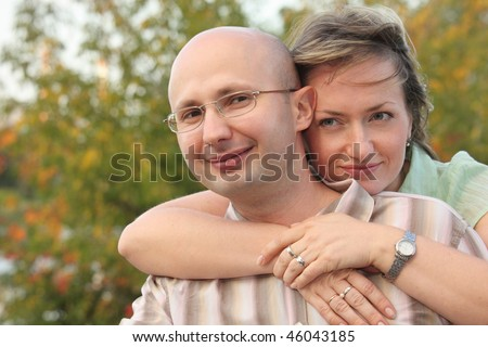 man and woman in fall park. woman is embracing her man - stock photo