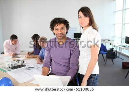 Man and woman in front of a business laptop - stock photo