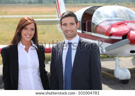 Man and woman in front of airplane - stock photo
