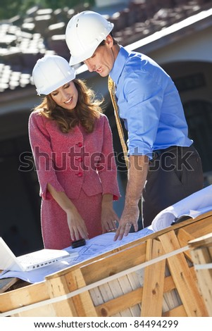 Man and woman in hard hat meeting on construction site with architect plans and a laptop computer. - stock photo