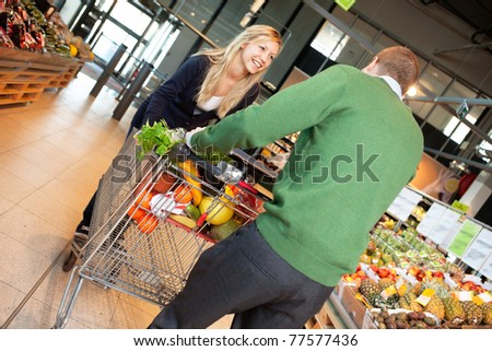 Man and woman in playful mood pushing shopping cart in shopping store - stock photo