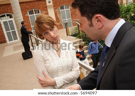 Man and woman in professional attire having a discussion outside of a public building. Woman's expression and body language is serious, possibly unhappy. - stock photo