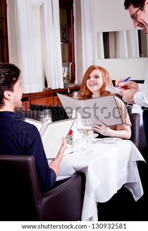 man and woman in restaurant waiter bring card and order food - stock photo