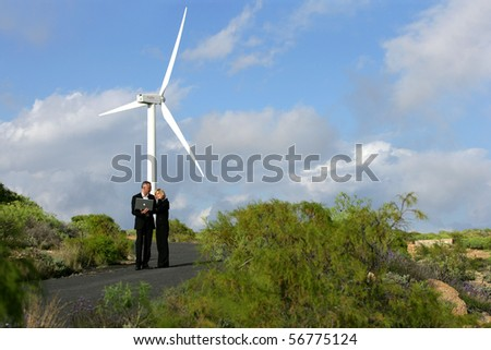 Man and woman in suit with a phone and a laptop computer in front of a wind turbine