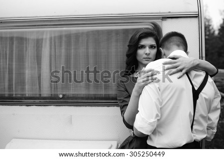 man and woman is hidden from view behind a trailer in the park with attractions - stock photo