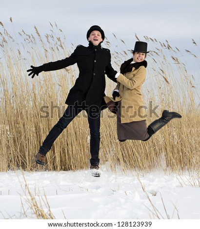Man and woman jump on frozen lake beach