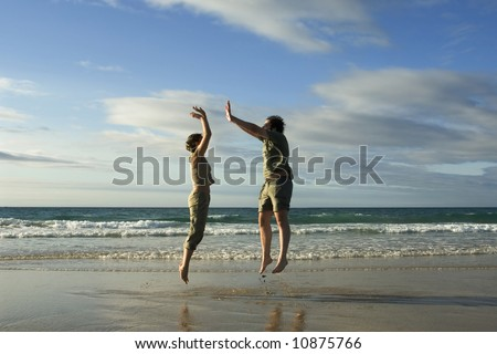 Man and woman jumping in a sunny beach - stock photo