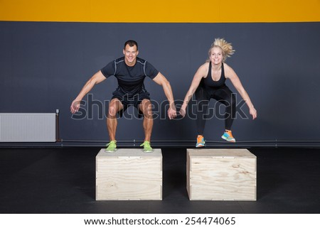 Man and woman jumping on a box - cross fit - stock photo