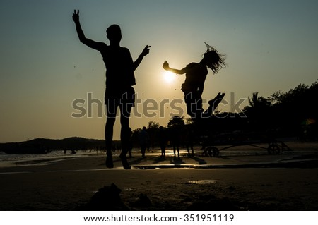 Man and Woman jumping on the beach during sunrise time,Silhouettes