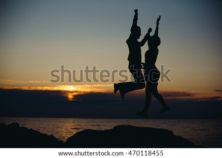 Man and woman jumps up on the shore by the sea