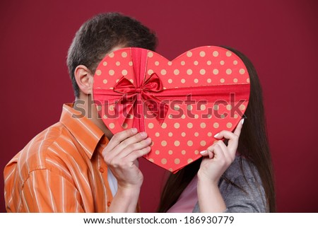Man and woman kissing in a heart-shaped box at red background - stock photo