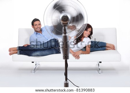 Man and woman laid on a sofa being ventilated by fan - stock photo