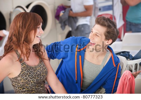 Man and woman laugh about his white shirt turned pink - stock photo