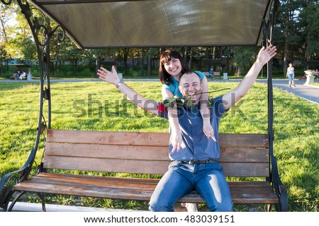 Man and woman laughing on the bench in the park