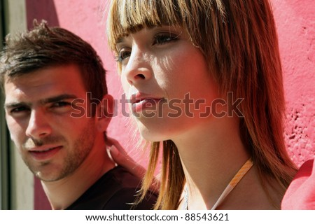 Man and woman leaning against a wall - stock photo