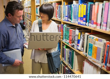 Man and woman looking at laptop standing in library - stock photo