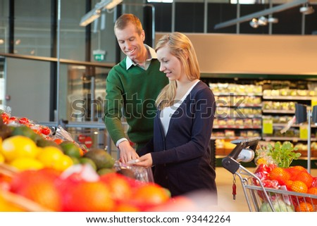Man and woman looking at products and smiling in shopping store - stock photo