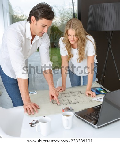 Man and woman looking at unrolled blueprints - stock photo
