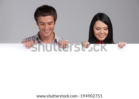 man and woman looking at white panel. Young Happy Couple Holding Placard Over White Background - stock photo