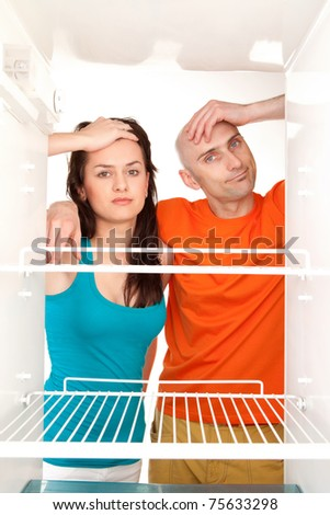 Man and woman looking into an empty refrigerator. - stock photo