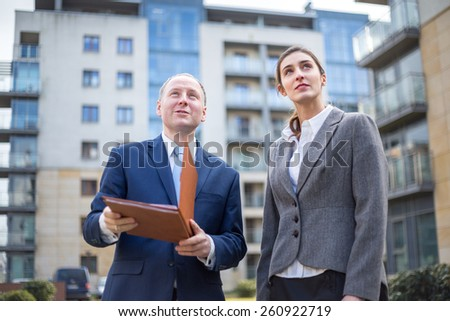 Man and woman looking up among new apartment buildings.