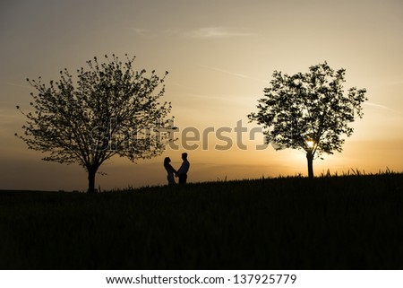 Man and Woman love silhouette in sunset - stock photo