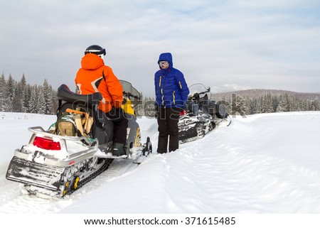 Man and woman made a stop while traveling by snowmobile in the mountains of the Southern Urals.