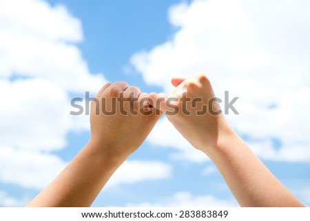 Man and woman making a pinkie promise with blue sky background - stock photo