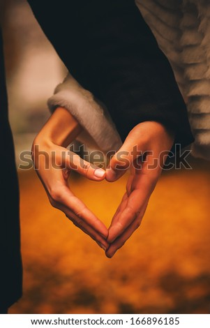 man and woman making heart with hands - stock photo