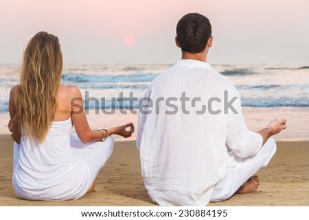Man and woman meditating in front of sea sitting in lotus position - stock photo