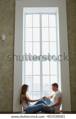 man and woman near a large window. They came to a new home, they are cozy, happy and love each other. Bought a new house or apartment, start a family life - stock photo