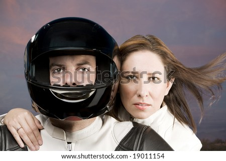 Man and woman on a motorcycle in studio - stock photo