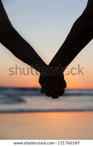 Man and woman on the beach accompany sunset of a sun