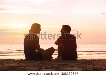 man and woman on the beach at sunset, young couple talking near the sea, dating or friendship concept - stock photo