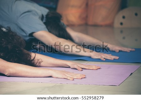 man and woman on yoga class indoor closeup of hands in relaxing pose