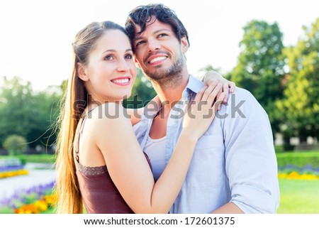 Man and woman or young couple making a trip as tourists in park hugging each other being in love