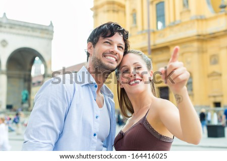 Man and woman or young couple making trip as tourists in Munich at the Odeon Church with city map on the tablet computer - stock photo