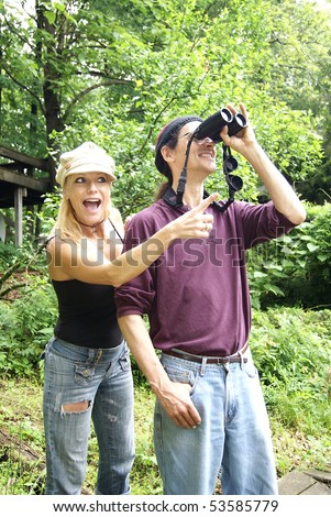Man and Woman outside with Binoculars - stock photo