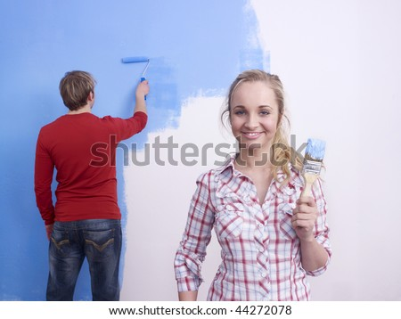 Man and woman painting a blue wall. - stock photo