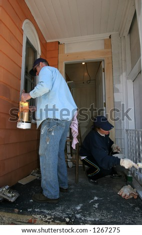man and woman painting exterior  of house - stock photo