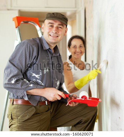 Man and woman paints wall at home together