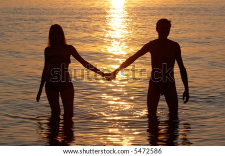 man and woman pair in water on sunset background - stock photo