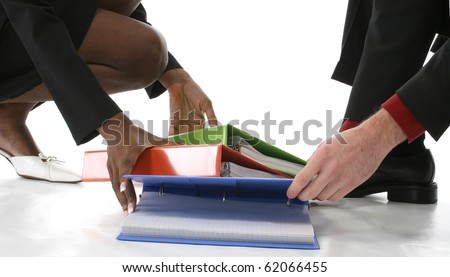 Man and woman picking up fallen binders from floor.  No faces. Shot over white background. - stock photo