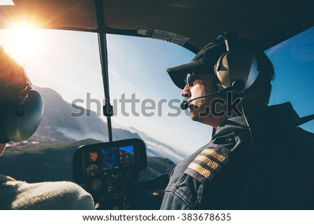 Man and woman pilots flying a helicopter on a sunny day. Inside shot of a helicopter. - stock photo